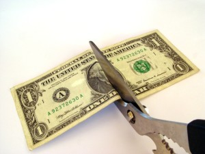 money being cut with scissors